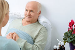 Young relative takes care of her sick grandfather stock image