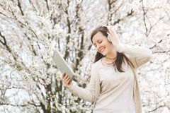 Young relaxed beautiful woman in light casual clothes with headphones listening music holding tablet pc computer in city royalty free stock photos