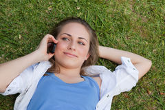Young relaxed blonde girl lying on her back while talking on the Royalty Free Stock Photos