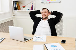 Young relaxed businessman with laptop in modern white office Royalty Free Stock Image