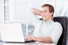 Young relaxed businessman working with laptop in Royalty Free Stock Images