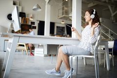 Having fun by workplace. Young relaxed businesswoman in casualwear listening to music in headphones while sitting by desk in office royalty free stock image