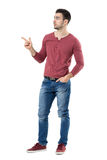 Young relaxed casual male presenter pointing finger at copyspace looking away. Full body length portrait isolated over white background royalty free stock image