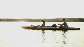 Young relaxed couple having rest on boat after rowing exercise. Stock footage stock video