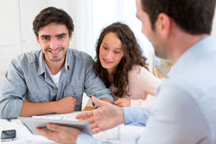 Young relaxed couple meeting a real estate agent. View of a young relaxed couple meeting a real estate agent royalty free stock photos