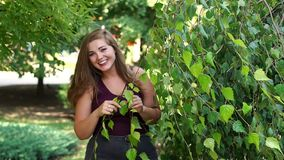 A young, relaxed girl with excess weight walks in the park in the summer. Portrait of a fat girl against a background of green trees stock footage