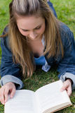 Young relaxed girl lying on the grass while reading a book Stock Image