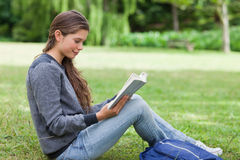 Young relaxed girl reading a book while sitting Stock Images