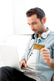 Young relaxed man buying music on a laptop. View of a Young relaxed man buying music on a laptop Royalty Free Stock Photos