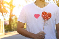 Young relaxed man is holding a red heart candy for girlfriend with sunshine effect on blurred background. Romance dating concept o Royalty Free Stock Image