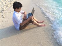 Young relaxed man with laptop sitting on the sandy beach with soft waves. Internet of things concept. Young relaxed man with laptop sitting on the sandy beach royalty free stock photography