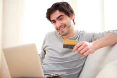 Young relaxed man paying online with credit card in sofa. View of a Young relaxed man paying online with credit card in sofa Stock Photos