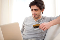Young relaxed man paying online with credit card in sofa Royalty Free Stock Images