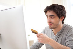 Young relaxed man paying online with his credit card Royalty Free Stock Photography