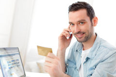 Young relaxed man paying online with his credit card. View of a Young relaxed man paying online with his credit card Royalty Free Stock Image