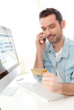 Young relaxed man paying online with his credit card. View of a Young relaxed man paying online with his credit card Stock Images