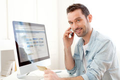 Young relaxed man paying online with his credit card. View of a Young relaxed man paying online with his credit card Stock Photo