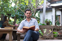 Young relaxed man reading book Stock Photo