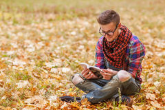Young relaxed man reading book in nature, back on tree, meadow b Stock Photo
