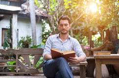 Young relaxed man reading book in nature Stock Images