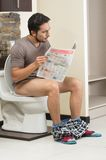 Young relaxed man sitting on the toilet reading. Young relaxed hispanic man sitting on the toilet reading the paper royalty free stock photos