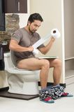 Young relaxed man sitting on the toilet reading Royalty Free Stock Image