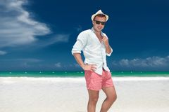 Young relaxed man standing on the beach, holding collar. And hand on waist against blue sky and ocean royalty free stock images