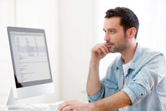 Young relaxed man using computer Stock Photography