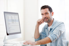 Young relaxed man using computer Stock Images