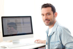 Young relaxed man using computer Royalty Free Stock Photography