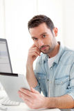 Young relaxed man using tablet at home Royalty Free Stock Images