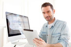 Young relaxed man using tablet at home Stock Photos