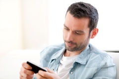 Young relaxed man writting text in the sofa Stock Photography
