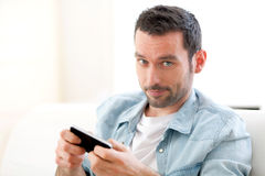 Young relaxed man writting text in the sofa Stock Photo