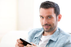 Young relaxed man writting text in the sofa Stock Image