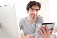 Young relaxed men at the office using tablet Royalty Free Stock Images
