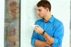 Young relaxed pensive businessman holding cup Stock Photography