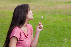 Young relaxed woman blowing a dandelion Royalty Free Stock Photo