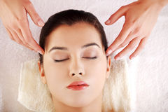 Young relaxed woman enjoy receiving massage. Beautiful young relaxed woman enjoy receiving massage at spa saloon Royalty Free Stock Images
