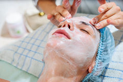 Young and relaxed woman getting a face massage. Stock Image