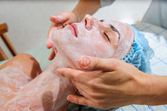 Young and relaxed woman getting a face massage. Stock Photos