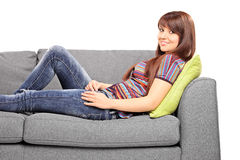 Young relaxed woman lying on a couch Stock Photography