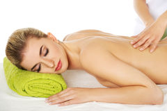 Young relaxed woman lying on a massage table and has massage. Royalty Free Stock Images