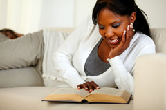 Young relaxed woman reading a book at home Stock Photography