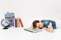Young relaxed woman student in denim clothes sleeping on laptop pc computer lying near globe, backpack, school books. Isolated on white background. Education in stock photos