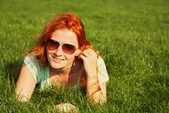 Relaxing redhead girl. Young relaxing redhead girl in sunglasses lying on the grass. woman relaxation outdoor stock photo