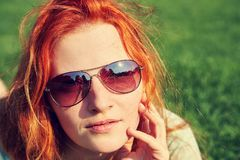 Young relaxing redhead girl in sunglasses lying on the grass. woman relaxation outdoor. Young relaxing redhead girl in sunglasses lying on the grass. woman royalty free stock image