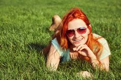 Young relaxing redhead girl in sunglasses lying on the grass. woman relaxation outdoor. Young relaxing redhead girl in sunglasses lying on the grass. woman royalty free stock photos