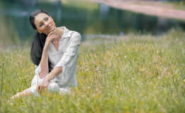 Young relaxing woman sitting in the grass Royalty Free Stock Photography