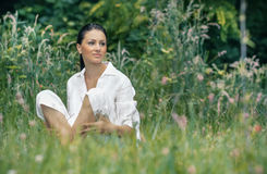 Young relaxing woman sitting on the grass Stock Image